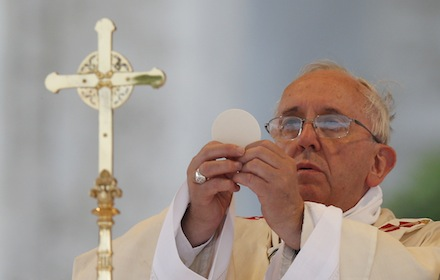 Pope Francis elevates the Eucharist as he celebrates Mass on the feast of Corpus Christi outside the Basilica of St. John Lateran in Rome June 19. (CNS photo/Paul Haring) (June 19, 2014) See POPE-PROCESSION and POPE-CORPUSCHRISTI June 19, 2014