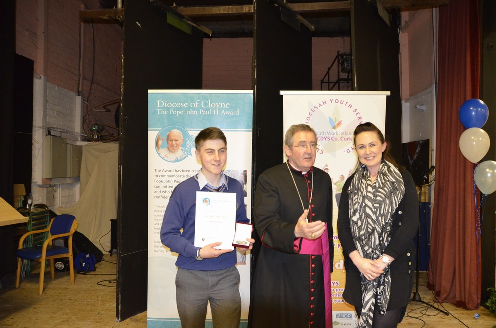 Denis O' Sullivan with Teacher Jamie Barrow From Scoil Mhuire Gan Smal Blarney with Bishop Crean